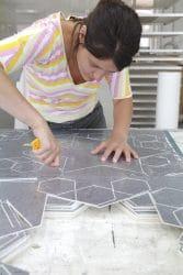 Eine Mitarbeiterin von Welter Wandunikate beim Erstellen einer edlen Tapete