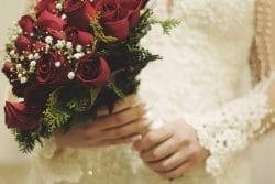 Ausschnitt einer Frau im Brautkleid und mit Brautstrauß