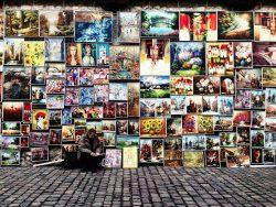 Ein Straßenkünstler vor einer Wand mit all seinen Werken