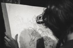 Eine Malerin vor der Leinwand beim Malen - von hinten abgebildet